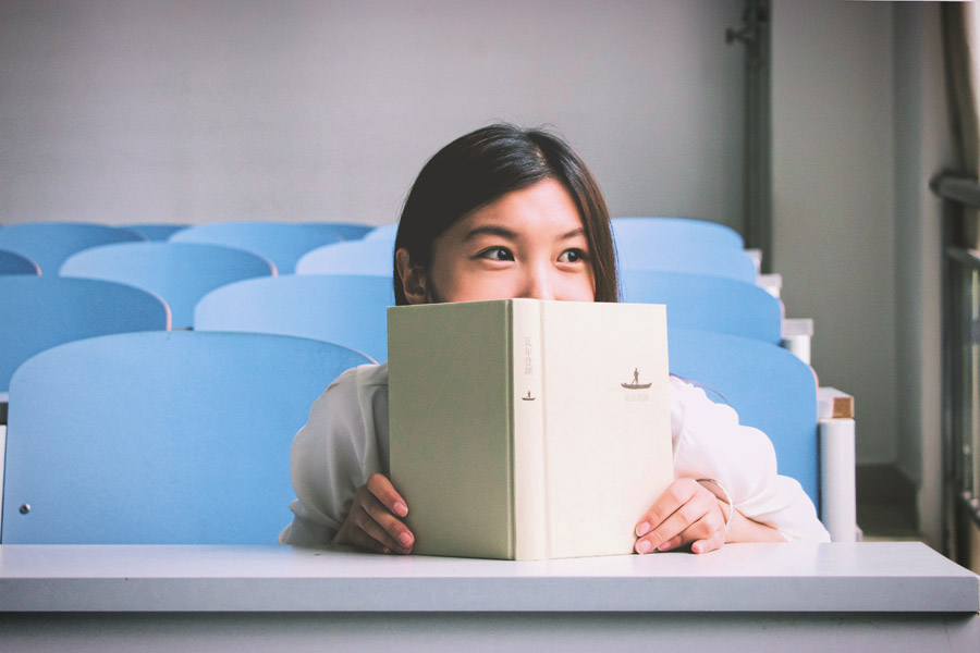 フリー写真 教室で本を立てている女子学生