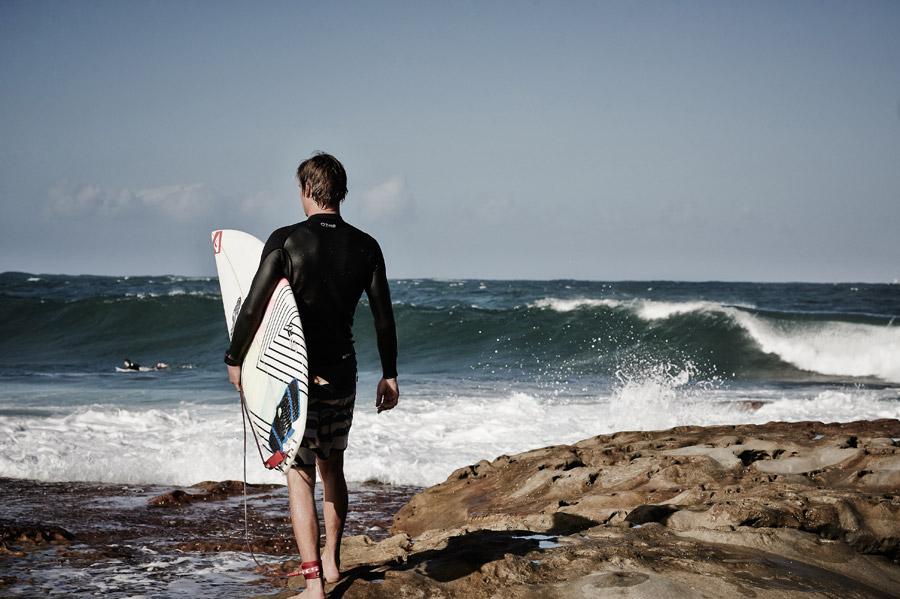 フリー写真 サーフボードを担いで海に向かうサーファー