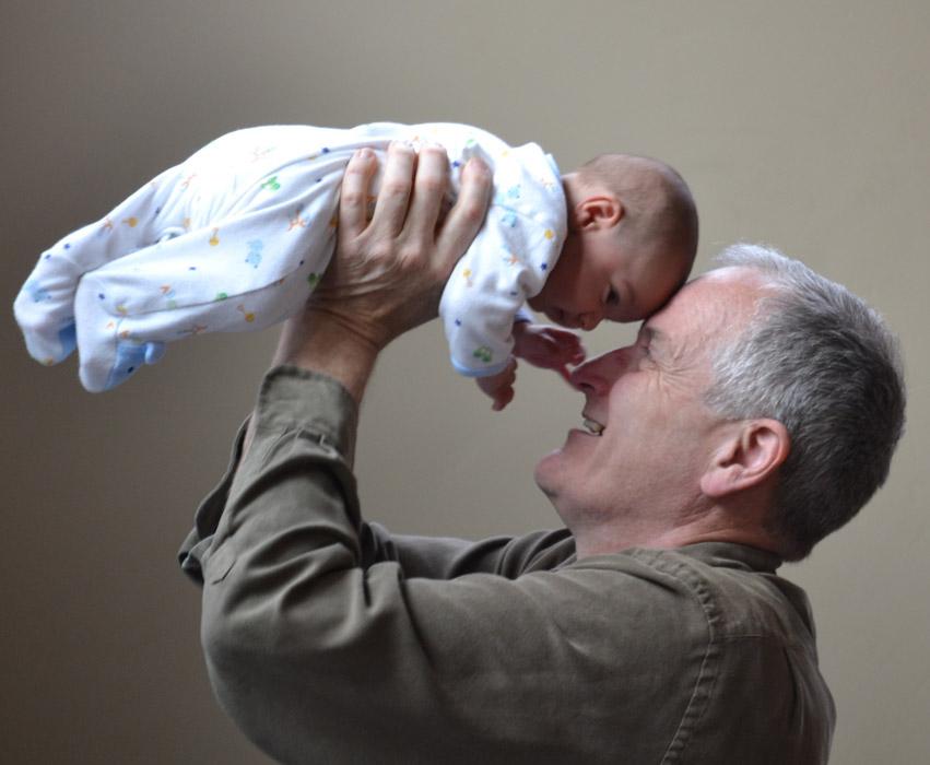 フリー写真 孫の赤ちゃんを抱き上げるおじいさん