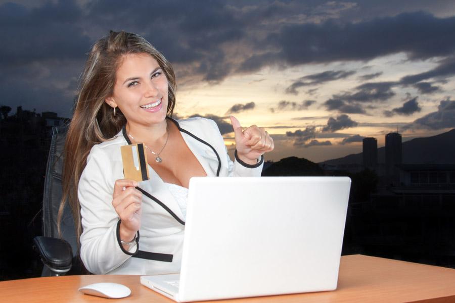 フリー写真 クレジットカードを持ちながらサムズアップしている外国人女性