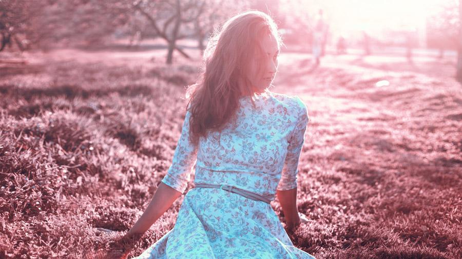 フリー写真 太陽の光と芝生の上に座る外国人女性