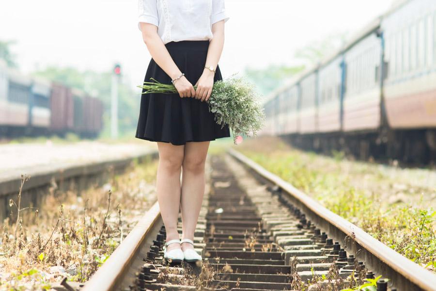 フリー写真 花束を持って線路の上に立つ女性