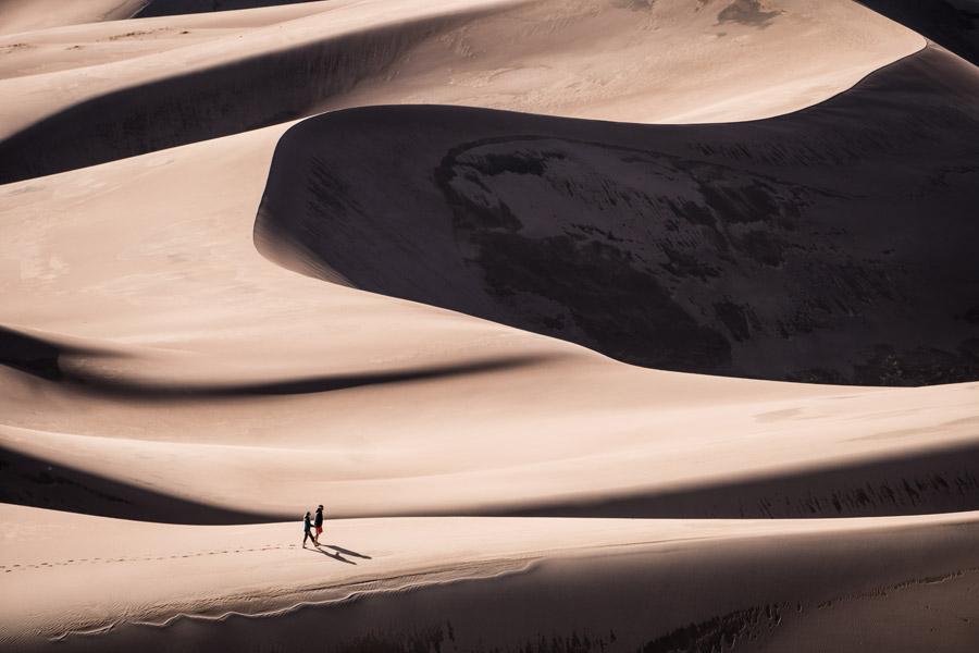 フリー写真 足跡をつけて砂漠を歩く二人