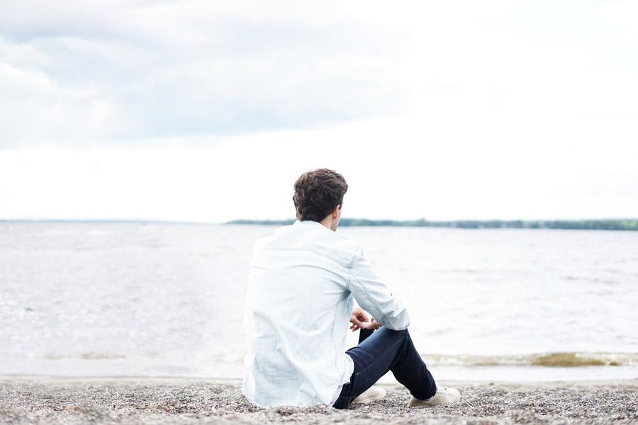 フリー写真 湖岸に座っている男性の後ろ姿