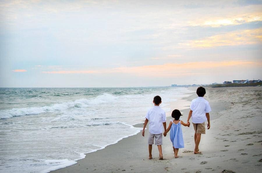 フリー写真 砂浜を手をつないで歩く三人の兄弟姉妹