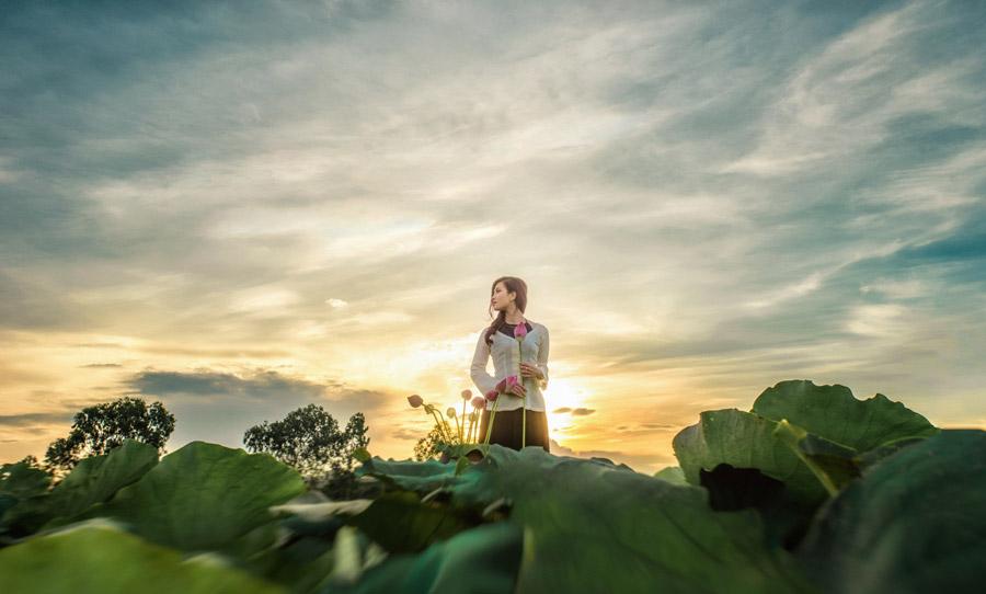 フリー写真 夕陽と蓮の蕾を持つ女性