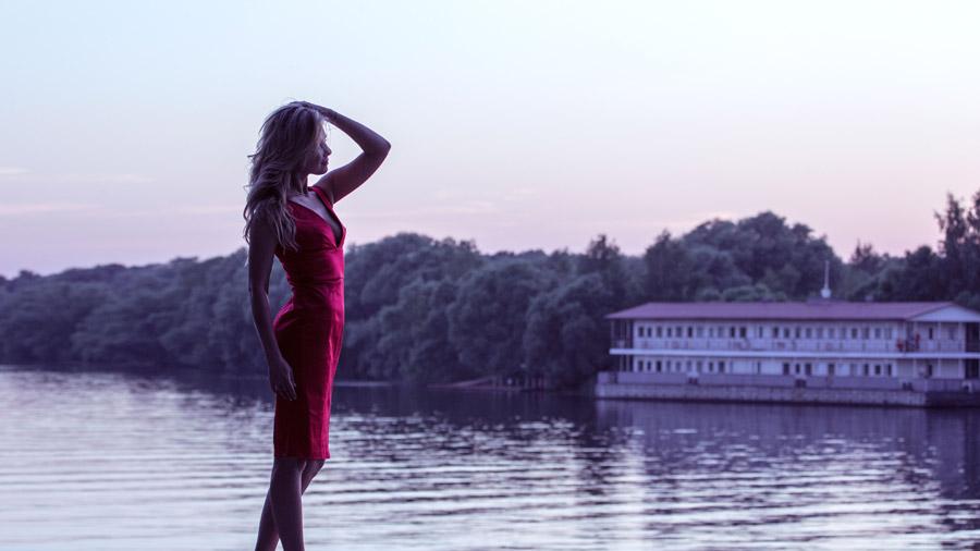 フリー写真 頭に手を当てるドレス姿の女性と湖