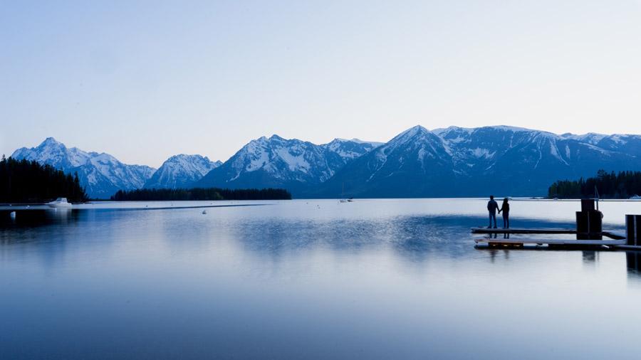 フリー写真 湖と山の風景と桟橋で手をつなぐカップル