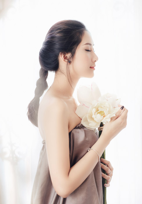 フリー写真 花を持って目を閉じている女性の横顔