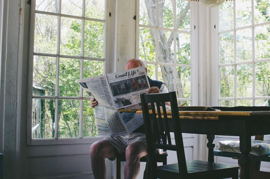 フリー写真 家の中で新聞を読んでいるおじいさん