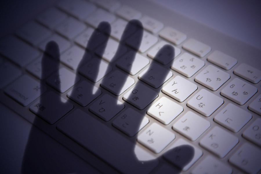 フリー写真 キーボードと手の影のネット犯罪のイメージ