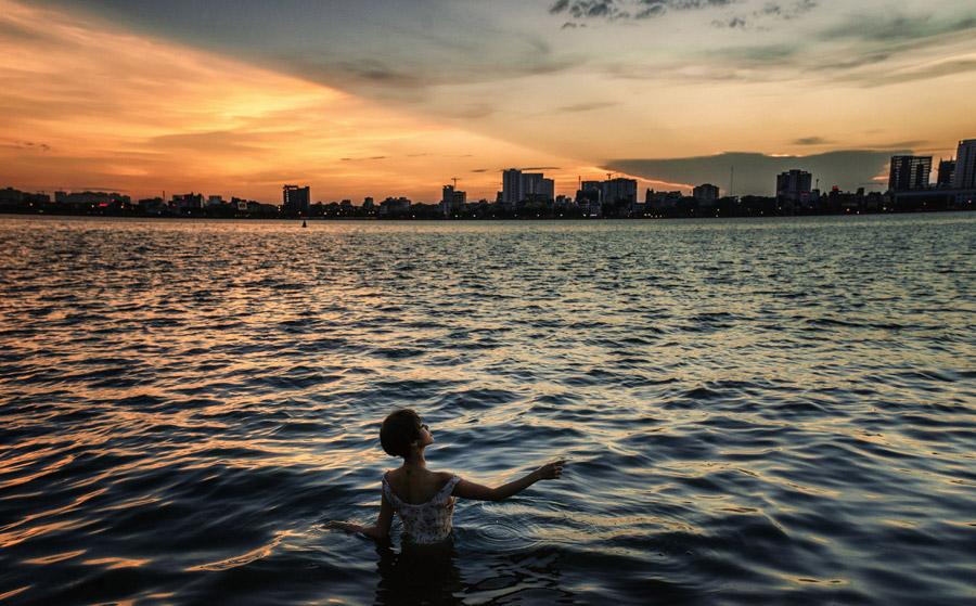 フリー写真 夕暮れの街と海の中の女性