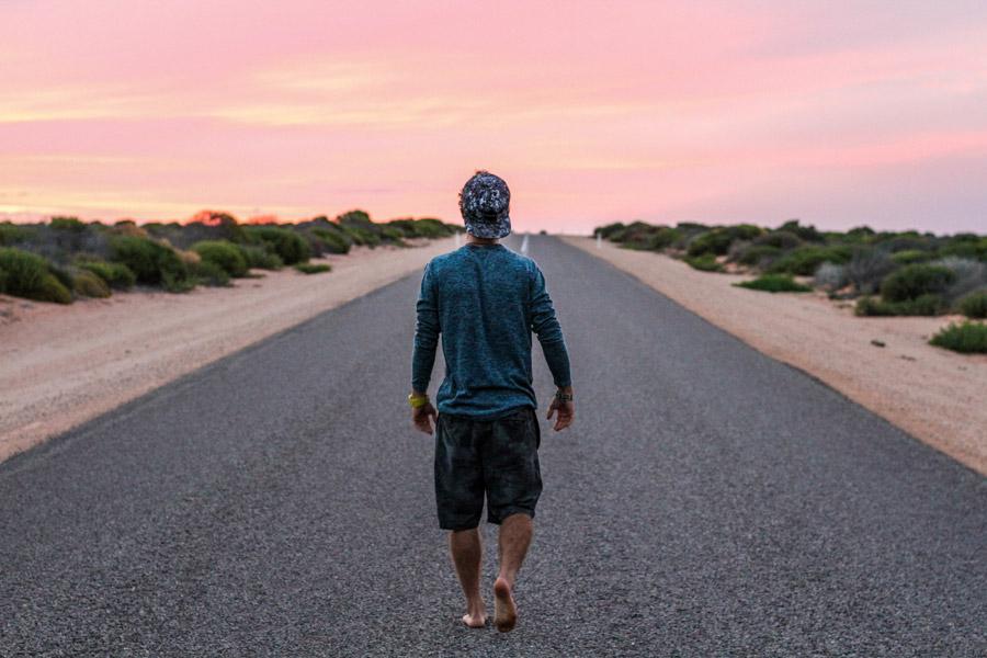 フリー写真 夕暮れの道路を裸足で歩く男性