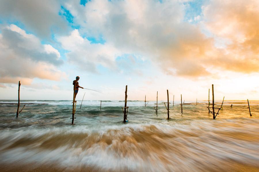 フリー写真 浅瀬の杭の上で魚を釣る人