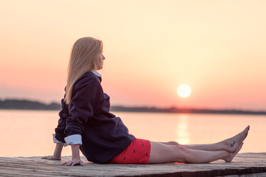 フリー写真 夕日と桟橋に足を伸ばして座る外国人女性