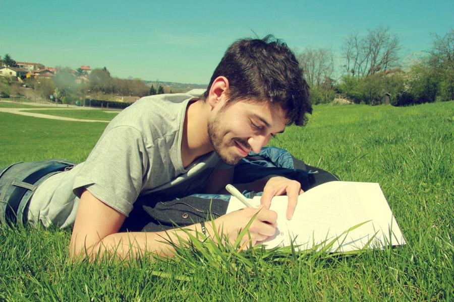 フリー写真 芝生の上に腹ばいになって書き物をしている外国人男性