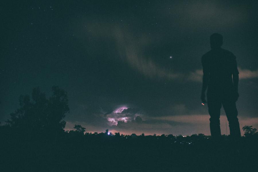 フリー写真 夜空に光るカミナリと人物のシルエット