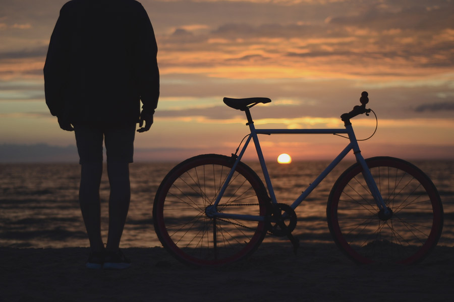 フリー写真 自転車と日の入りを見ている人物のシルエット