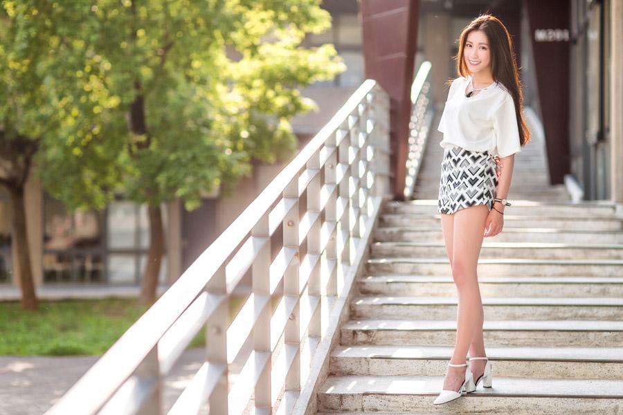 フリー写真 ショートパンツ姿で階段に立っている女性の全身ショット