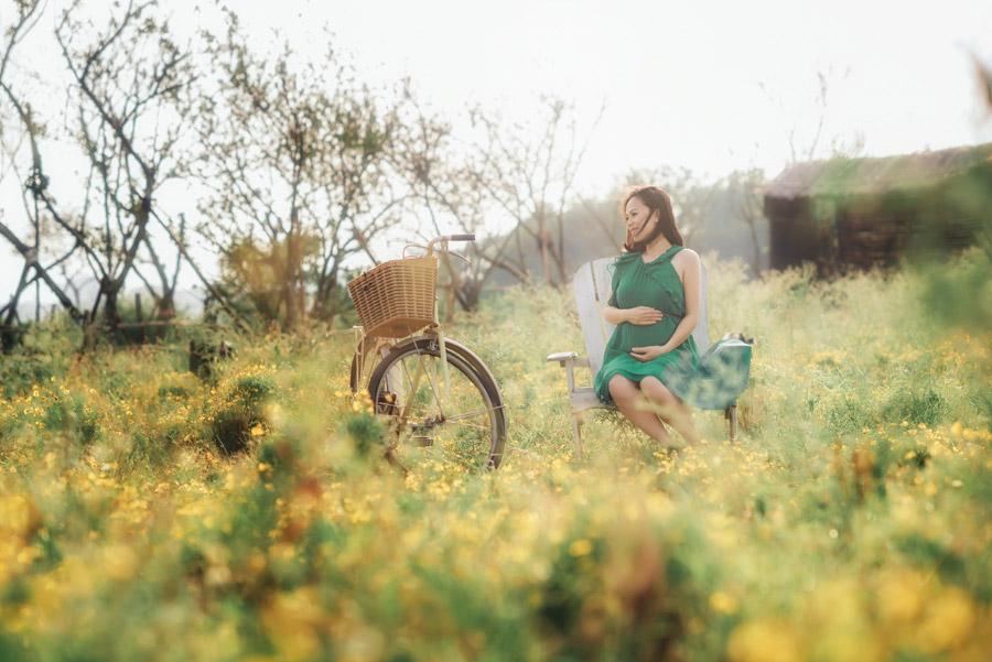 フリー写真 椅子に座る妊婦と草花と自転車