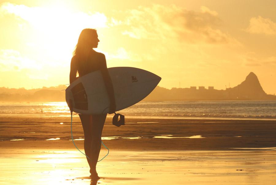 フリー写真 夕暮れのビーチとサーフボードを抱える女性サーファー