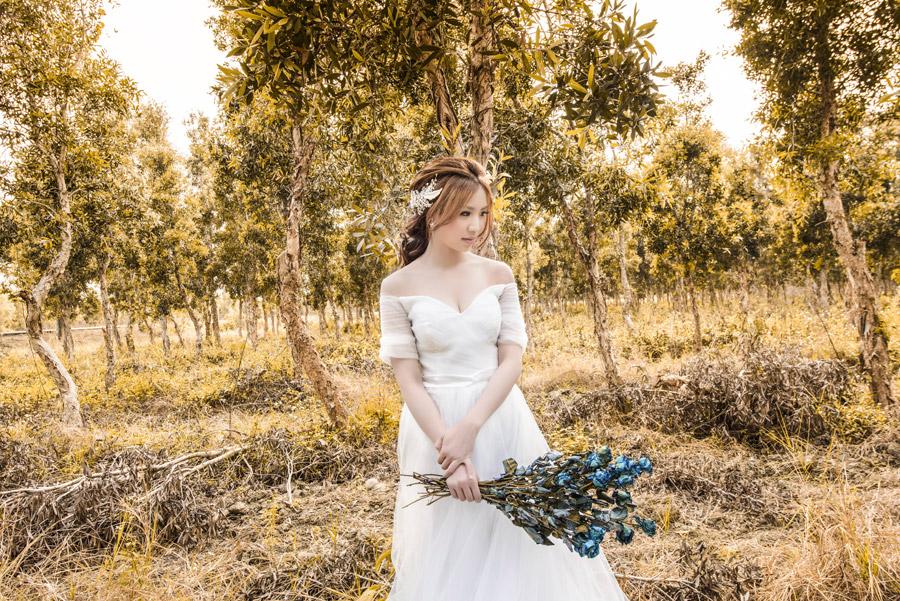 フリー写真 木々とドレス姿で花束を持つ女性