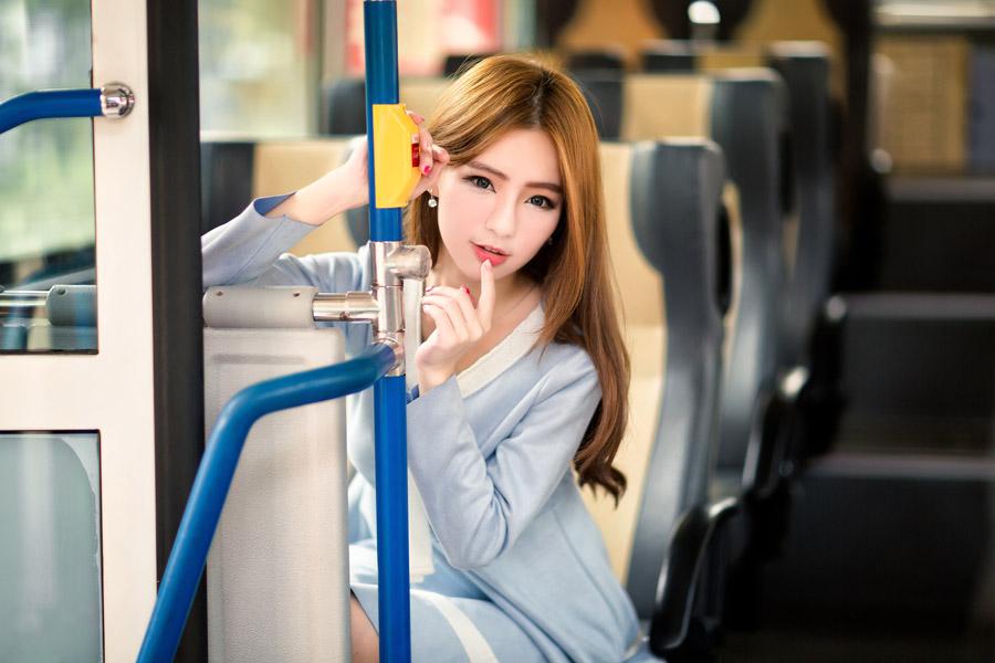 フリー写真 バスに乗って唇に指を当てている女性
