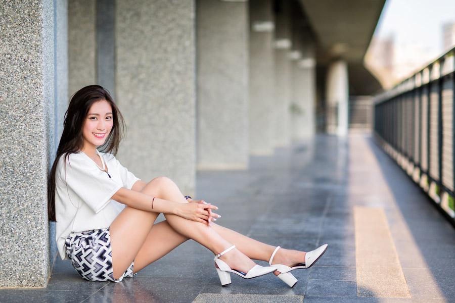 フリー写真 建物の床に膝を抱えて座る女性