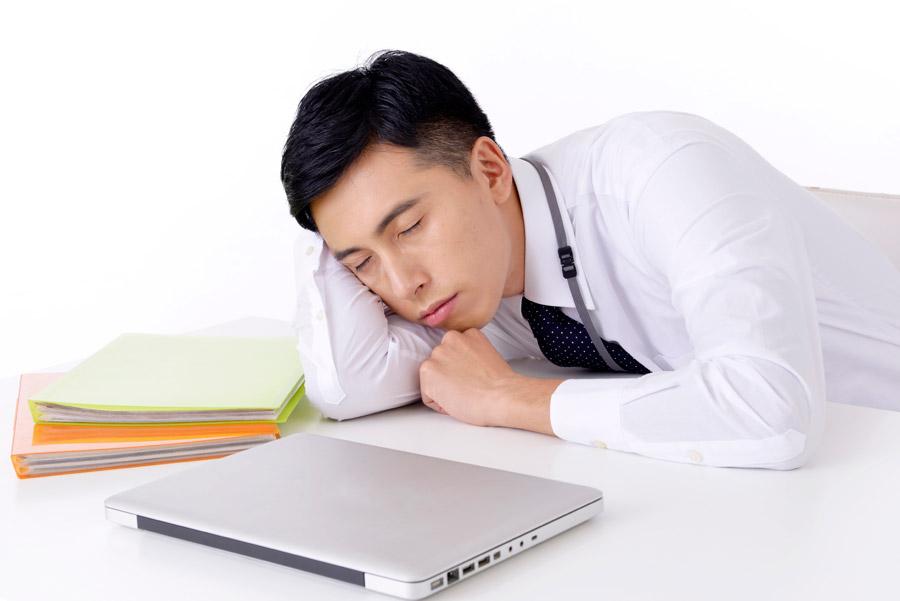 フリー写真 仕事をさぼって寝ているサラリーマン男性