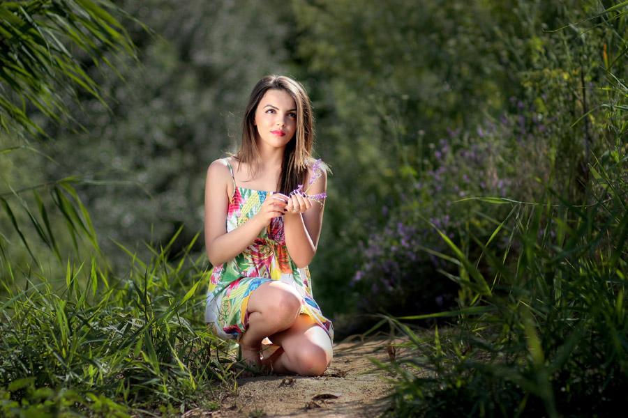 フリー写真 しゃがんで花を摘む外国人女性
