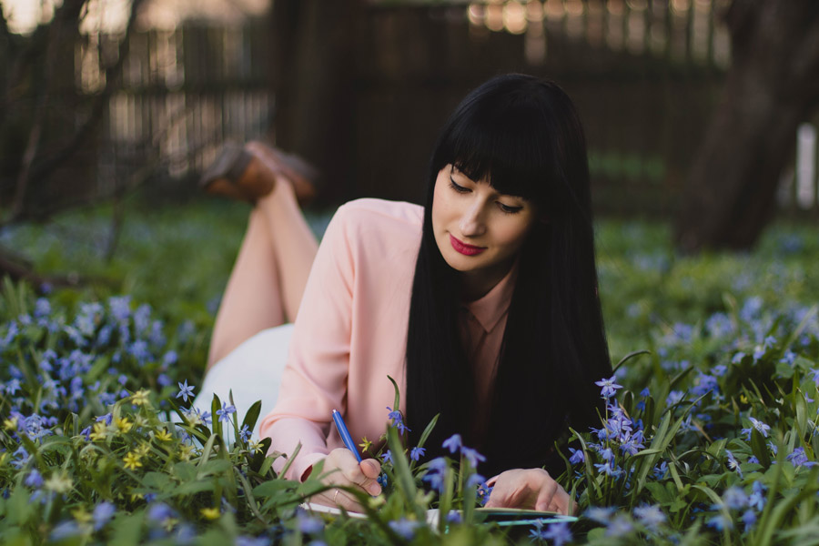 フリー写真 草花と腹這いになって書き物をしている外国人女性