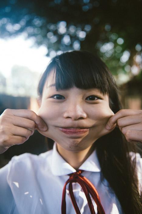 フリー写真 ほっぺを引っ張って変顔する女子学生
