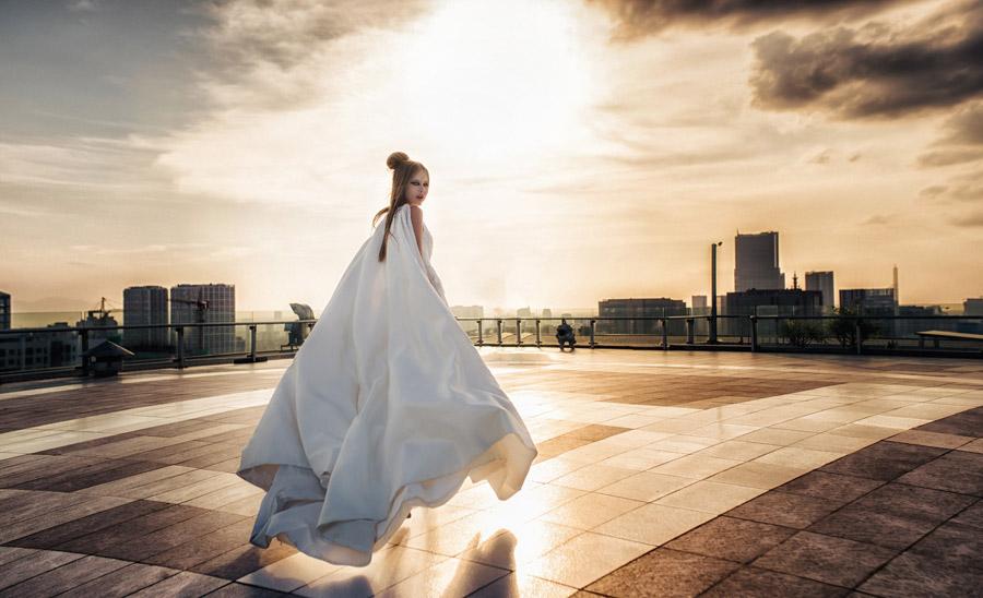 フリー写真 マント風のドレス姿で夕暮れの屋上に立つ女性