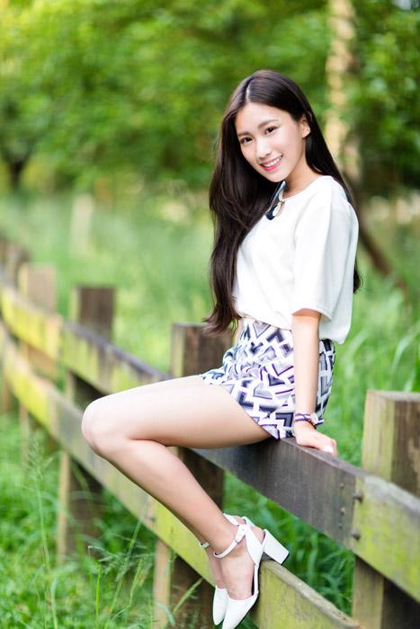 フリー写真 柵の上に腰掛ける女性
