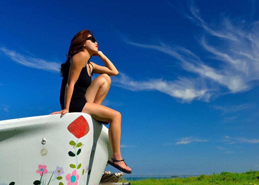 フリー写真 青空とボートの先に腰掛ける女性