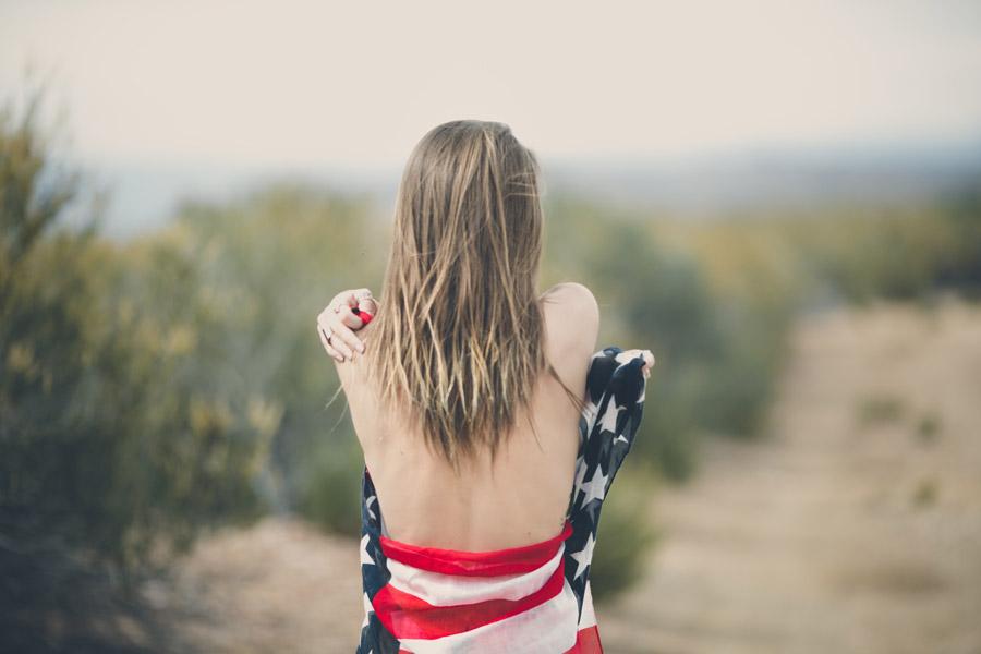 フリー写真 星条旗に包まれる女性の後ろ姿