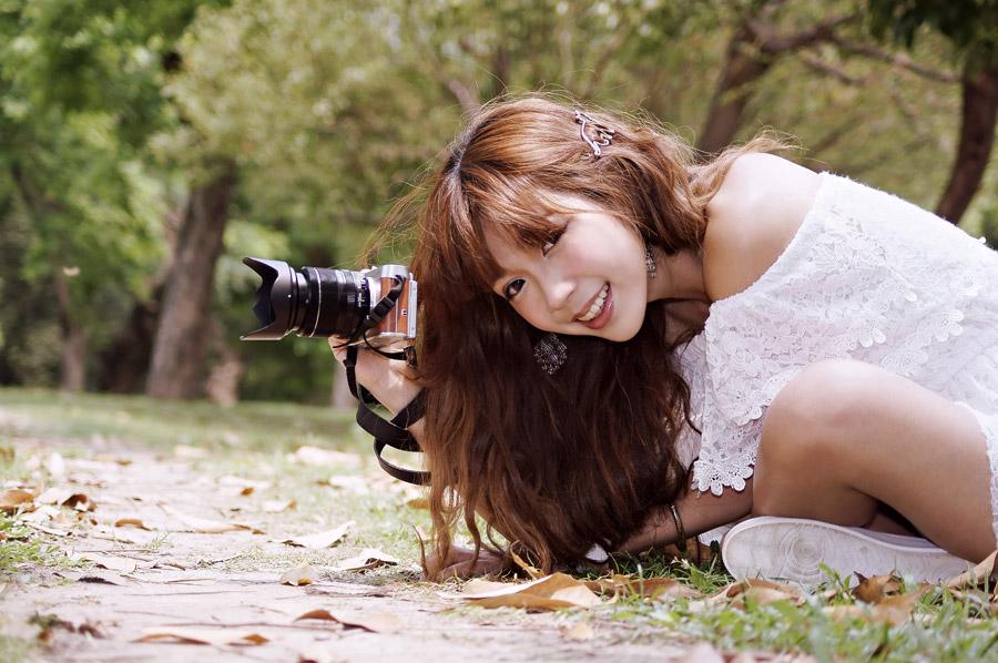 フリー写真 地面に座りながら写真を撮影する女性