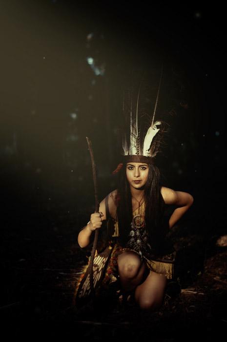 フリー写真 インディアンの格好をして片膝をつく外国人女性