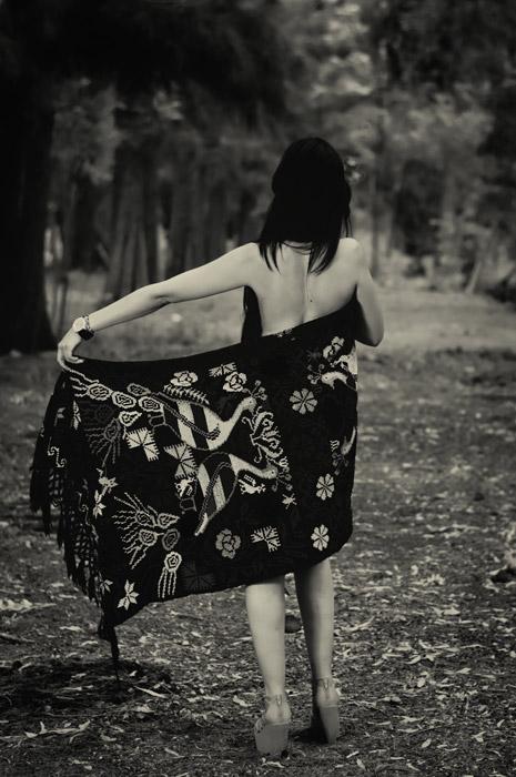 フリー写真 森の中でブランケットに身を包む女性の後ろ姿
