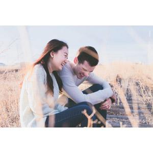 フリー写真, 人物, カップル, 夫婦, 笑う(笑顔), 座る(地面), 寄り添う, 枯れ草