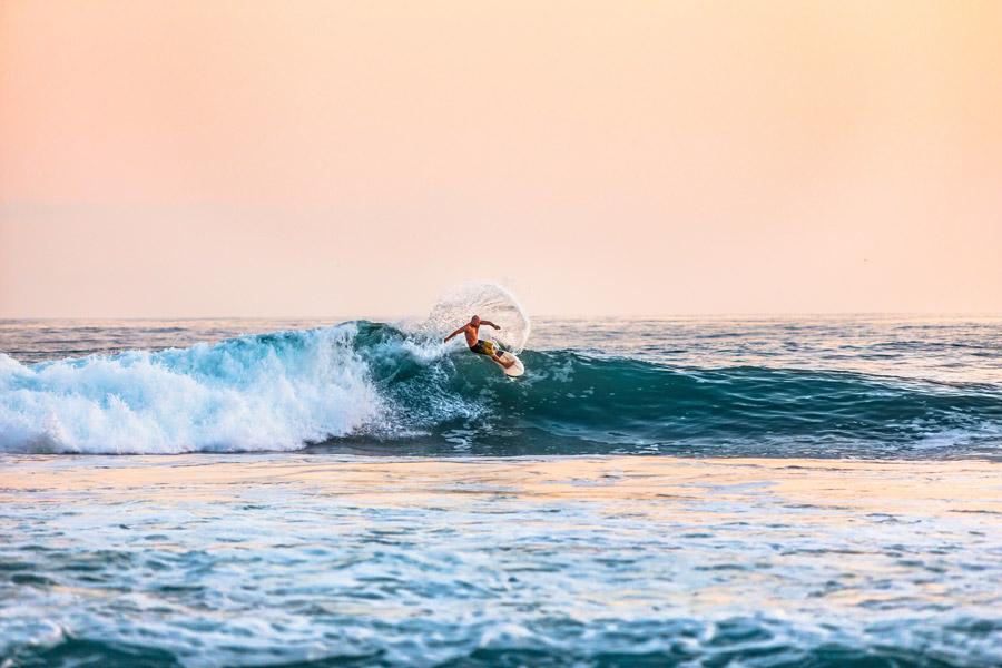 フリー写真 夕暮れの海でサーフィンをしている男性