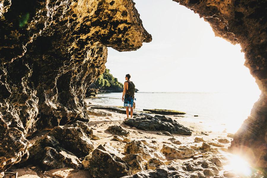 フリー写真 海食された岩とビーチに立つ男性