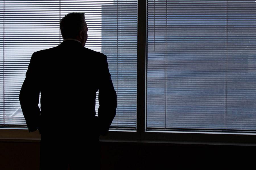 フリー写真 窓の外を眺めるビジネスマンの後ろ姿