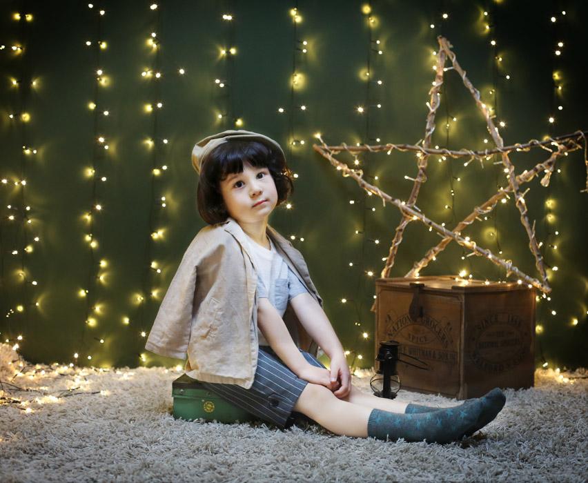 フリー写真 電飾と座っている子供のポートレイト