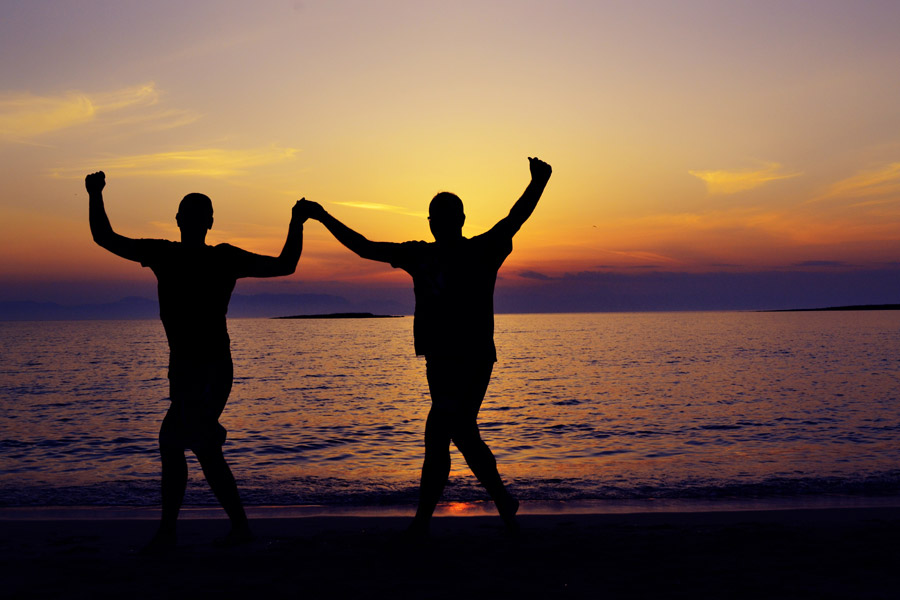 フリー写真 夕暮れのビーチでガッツポーズしている二人の人物