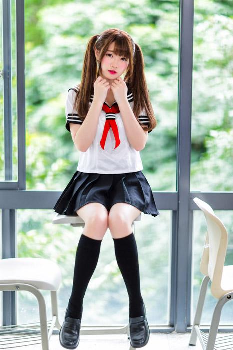 フリー写真 セーラー服姿で机の上に座るツインテールの女子高生