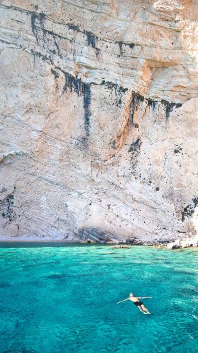 フリー写真 崖と海に浮かぶ人の風景