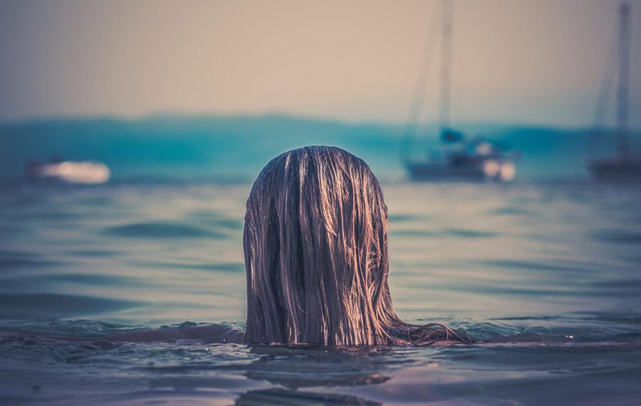 フリー写真 海に入っている女性の後ろ姿