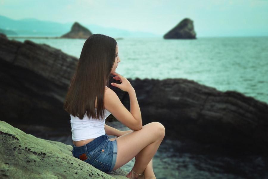 フリー写真 海岸に座って海を眺める外国人女性