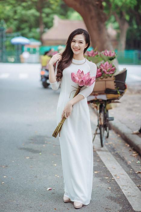 フリー写真 露店で蓮の花を買ったアオザイ姿の女性